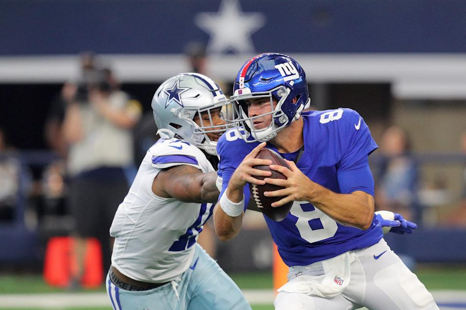 Daniel Jones #8 of the New York Giants keeps the ball and is pursued by Micah Parsons #11 of the Dallas Cowboys during the second quarter at AT&T Stadium on October 10, 2021 in Arlington, Texas.