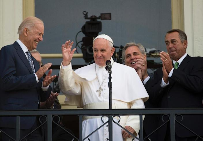 Pope Francis waves next to US Vice President Joe Biden (L) and John Boehner (R), on a balcony after speaking at the US Capitol building in Washington, DC on September 24, 2015 (AFP Photo/Andrew Caballero-Reynolds)