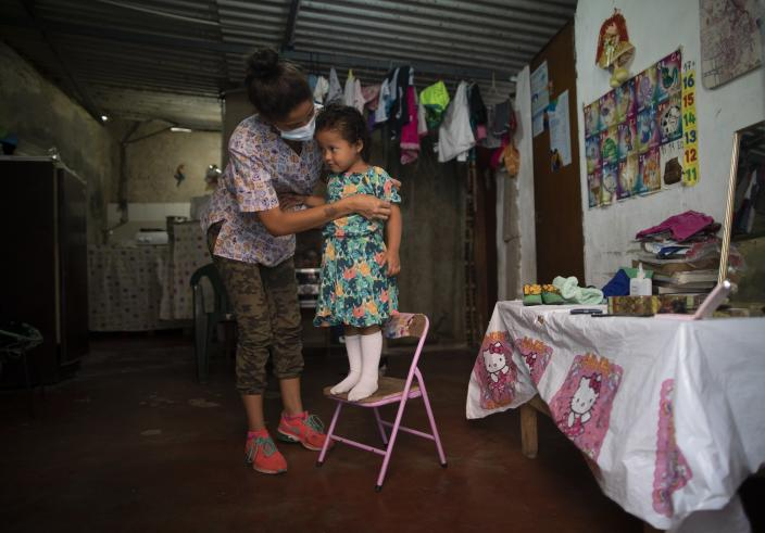 Elena Escalante helps her 3-year-old daughter Zaii prepare for a homespun beauty pageant in the Antimano neighborhood of Caracas, Venezuela, Friday, Feb. 5, 2021. Neighbors in the hillside barrio gathered for the carnival pageant tradition to select their child queen for the upcoming festivities. (AP Photo/Ariana Cubillos)