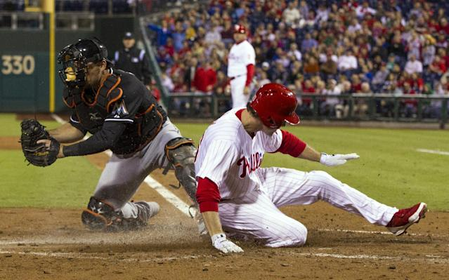 Philadelphia Phillies' Chase Utley, right, slides into home on a single by Carlos Ruiz as Miami Marlins catcher Jeff Mathis stops the relay throw during the third inning of a baseball game, Tuesday, Sept. 17, 2013, in Philadelphia. (AP Photo/Chris Szagola)