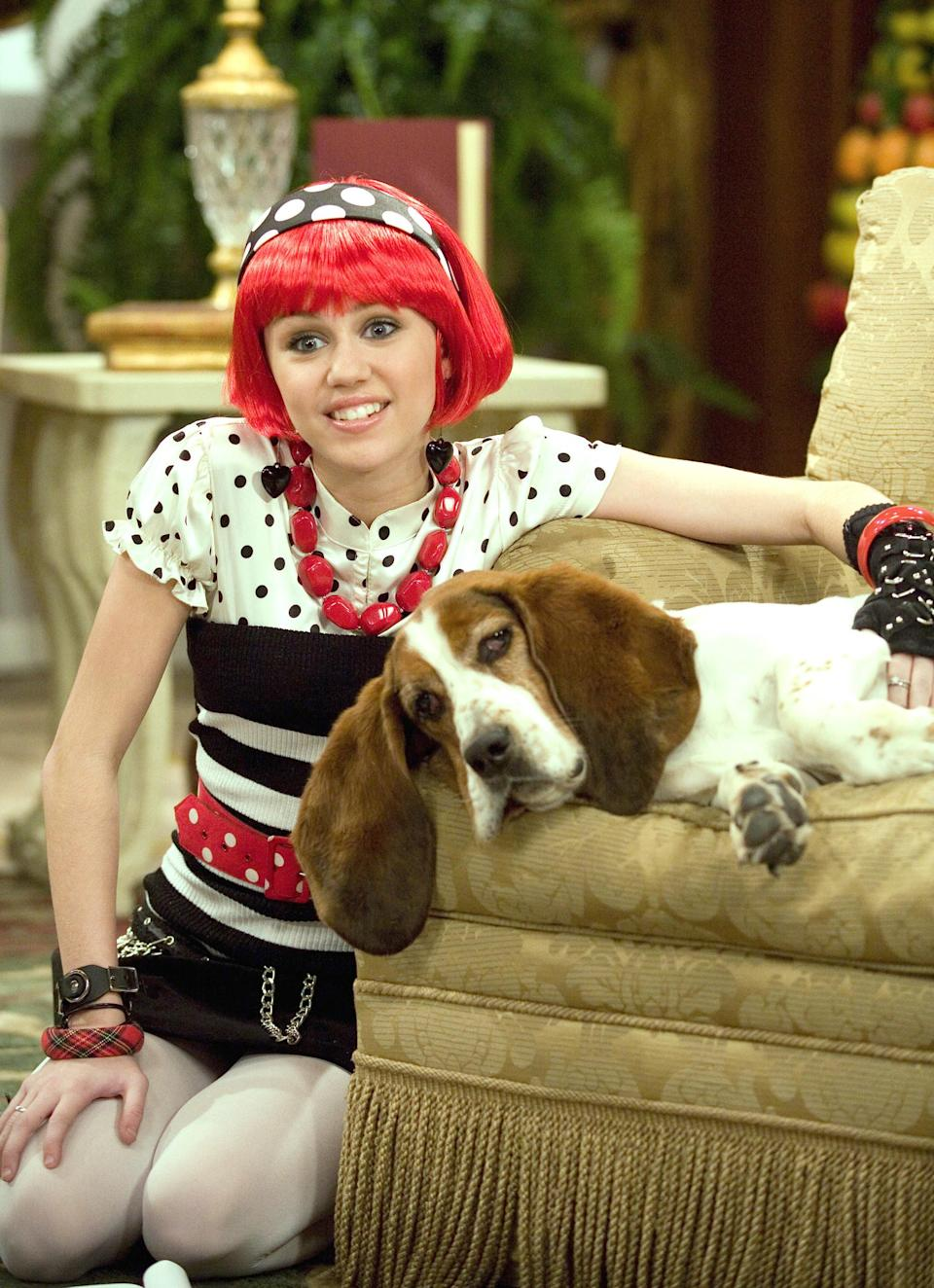 Miley in a Lola outfit with a striped sweater tipe top, a skirt with a chain belt, a puff sleeve polka top short sleeve top, a chunky necklace and bracelets, and tights