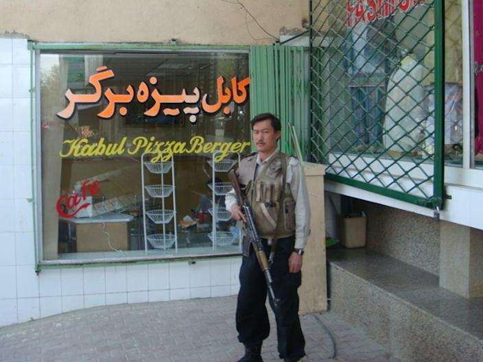 A man with a rifle stands in front of a restaurant window