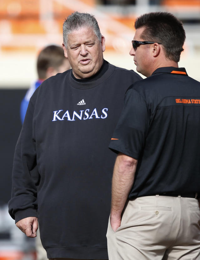 Oklahoma State head coach Mike Gundy, right, talks with Kansas head coach Charlie Weis, left, before the start of an NCAA college football game in Stillwater, Okla., Saturday, Nov. 9, 2013. (AP Photo/Sue Ogrocki)