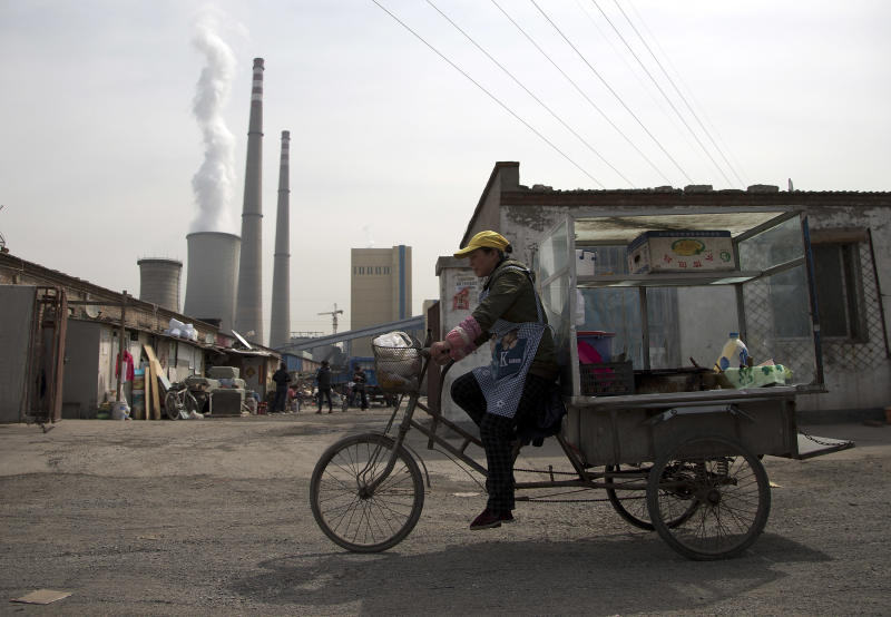 A vendor rides his tricycle near a coal-fired power plant in Beijing on Friday, April 12, 2013. China, the world's largest producer of carbon dioxide, is directly feeling the man-made heat of global warming, scientists conclude in the first study to link the burning of fossil fuels to one country's rise in its daily temperature spikes. (AP Photo/Andy Wong)