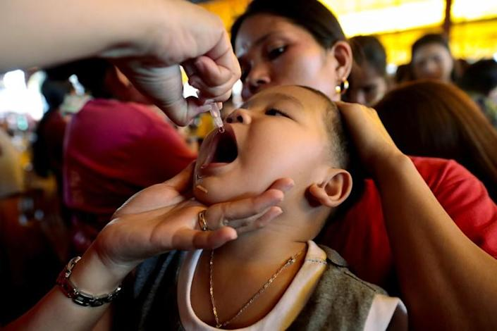FILE PHOTO: A child receives free polio vaccine during a government-led mass vaccination program in Quezon City