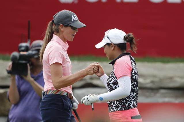 Jasmine Suwannapura, right, gets a fist bump from Cydney Clanton after her drive on the 18th tee during the final round of the Dow Great Lakes Bay Invitational golf tournament, Saturday, July 20, 2019, in Midland, Mich. (AP Photo/Carlos Osorio)