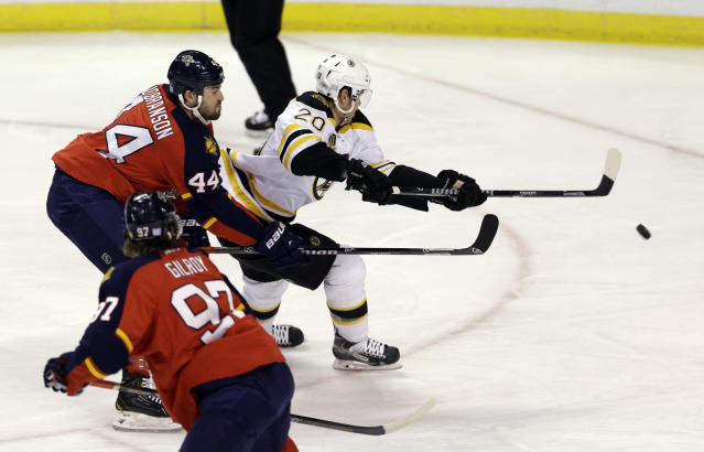 Boston Bruins left wing Daniel Paille (20) takes a shot and scores as Florida Panthers defenseman Erik Gudbranson (44) and Florida Panthers defenseman Matt Gilroy (97) defend in the first period of an NHL hockey game, Thursday, Oct. 17, 2013, in Sunrise, Fla. (AP Photo/Alan Diaz)