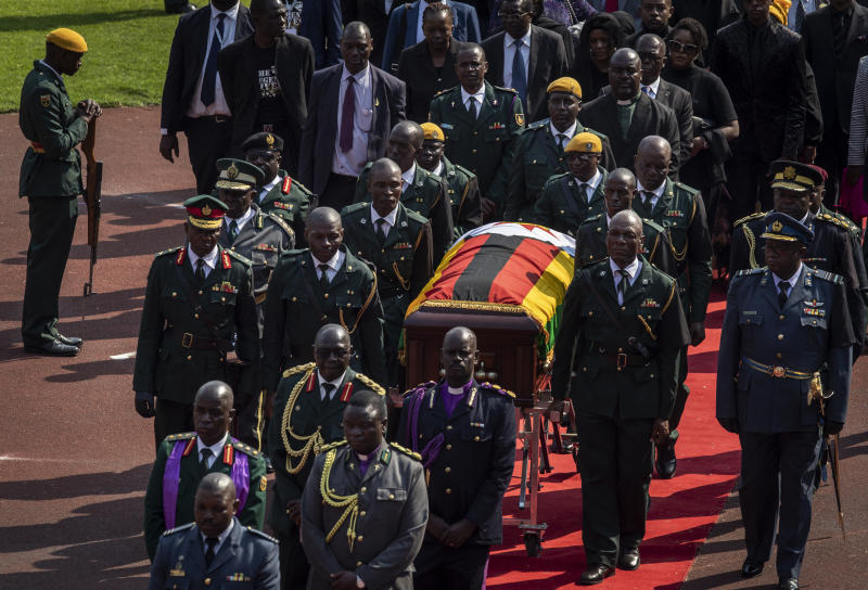 The casket of former president Robert Mugabe is escorted by military officers and followed by family and dignitaries as it departs after a state funeral at the National Sports Stadium in the capital Harare, Zimbabwe Saturday, Sept. 14, 2019. African heads of state and envoys gathered to attend a state funeral for Zimbabwe's founding president, Robert Mugabe, whose burial has been delayed for at least a month until a special mausoleum can be built for his remains. (AP Photo/Ben Curtis)