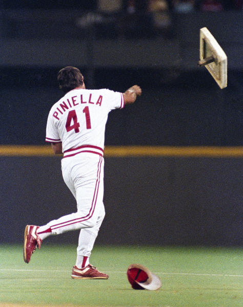FILE - In this April 21, 1990, file photo, Cincinnati Reds manager Lou Piniella tosses first base into right field after he was ejected for arguing a call at first during a baseball game against the Chicago Cubs at Riverfront Stadium in Cincinnati. (AP Photo/David Kohl, File)