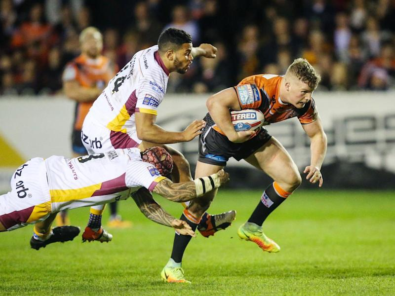 Adam Milner breaks through the Huddersfield line to score a try for Castleford (PA)