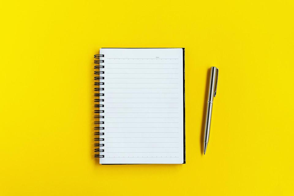 Note Pad and Pen on Yellow background