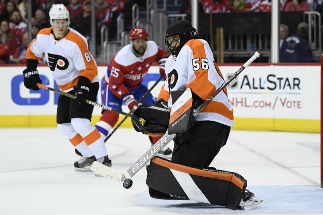 Philadelphia Flyers goaltender Mike McKenna (56) stops the puck during the second period of an NHL hockey game as Washington Capitals right wing Devante Smith-Pelly (25) watches, Tuesday, Jan. 8, 2019, in Washington. Also seen is Flyers defenseman Robert Hagg (8). (AP Photo/Nick Wass)