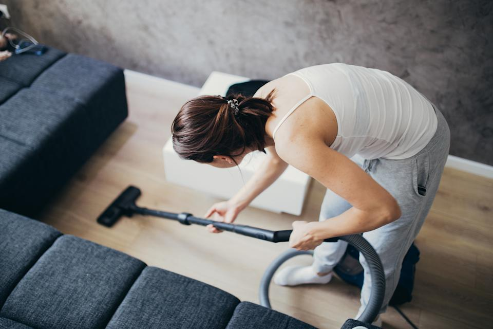 Woman cleaning the floor in living room with vacuum cleaner.