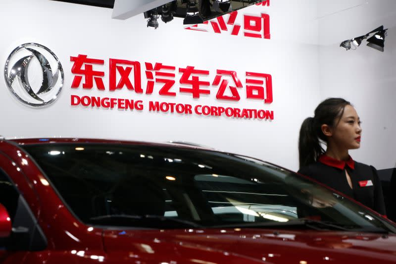 A hostess poses next to Dongfeng Motor Corp A9 sedan at the Auto China 2016 auto show in Beijing