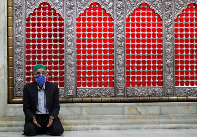 An Iraqi man wearing a protective mask, prays inside the Imam Hussein shrine in the holy city of Kerbala