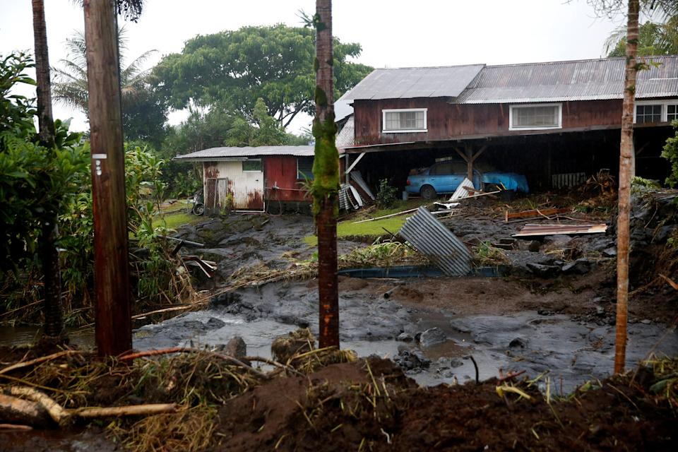<p>Mud and debris litter a backyard as a result of flooding caused by Hurricane Lane in Hilo, Hawaii, Aug. 25, 2018. (Photo: Terray Sylvester/Reuters) </p>