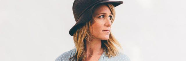 woman with short blonde hair wearing a blue shirt and a brown hat is looking away over her shoulder and standing against a white wall
