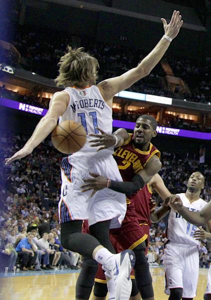 Cleveland Cavaliers' Kyrie Irving (2) passes the ball around Charlotte Bobcats' Josh McRoberts (11) during the first half of an NBA basketball game in Charlotte, N.C., Friday, Nov. 1, 2013. (AP Photo/Chuck Burton)