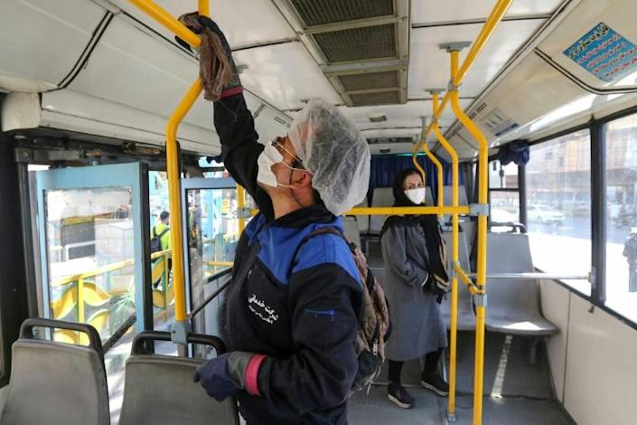 A municipality worker cleans a bus in Tehran to halt the the spread of coronavirus (AFP Photo/ATTA KENARE)