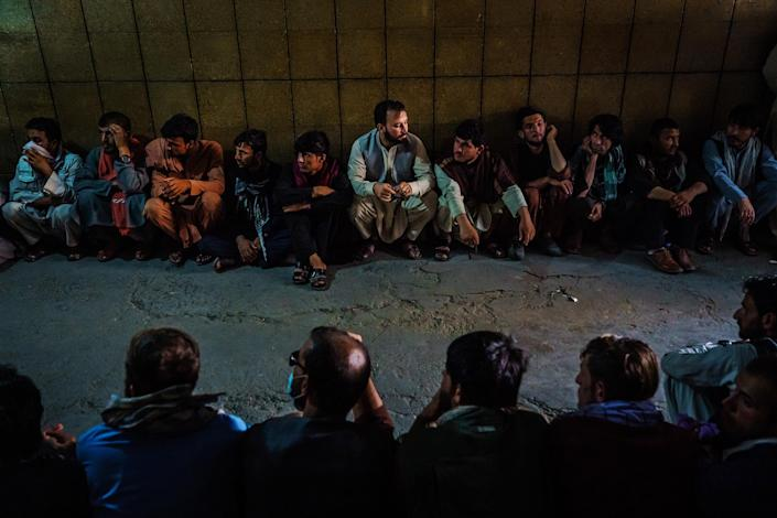 """Hundreds of Afghans, guarded by Taliban militants, line up to withdraw money from banks that are slowly reopening after Taliban took control of the country, in Kabul on Sept. 5.<span class=""""copyright"""">Marcus Yam—Los Angeles Times/Getty Images</span>"""