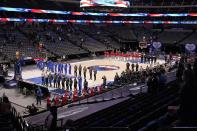 The Dallas Mavericks and Atlanta Hawks, along with a limited fan attendance stand during the playing of the national anthem before the first half of an NBA basketball game in Dallas, Wednesday, Feb. 10, 2021. (AP Photo/Tony Gutierrez)