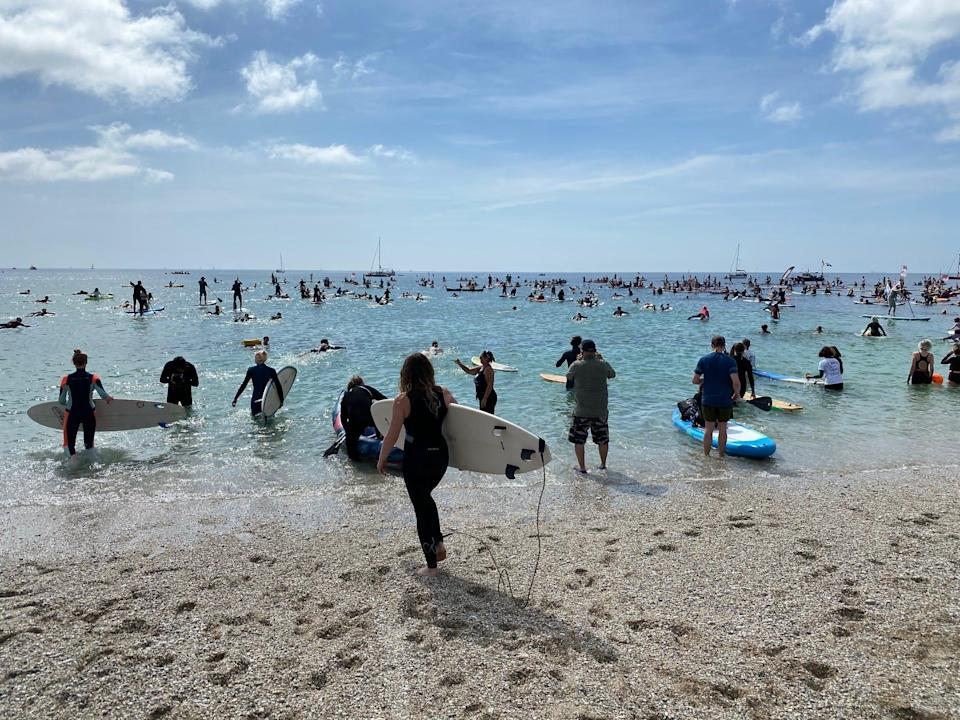 Waters sports enthusiasts takes to the sea at Gyllyngvase Beach, Cornwall, in England, to protest how oceans are impacted by climate change. Photo: June 12, 2021.
