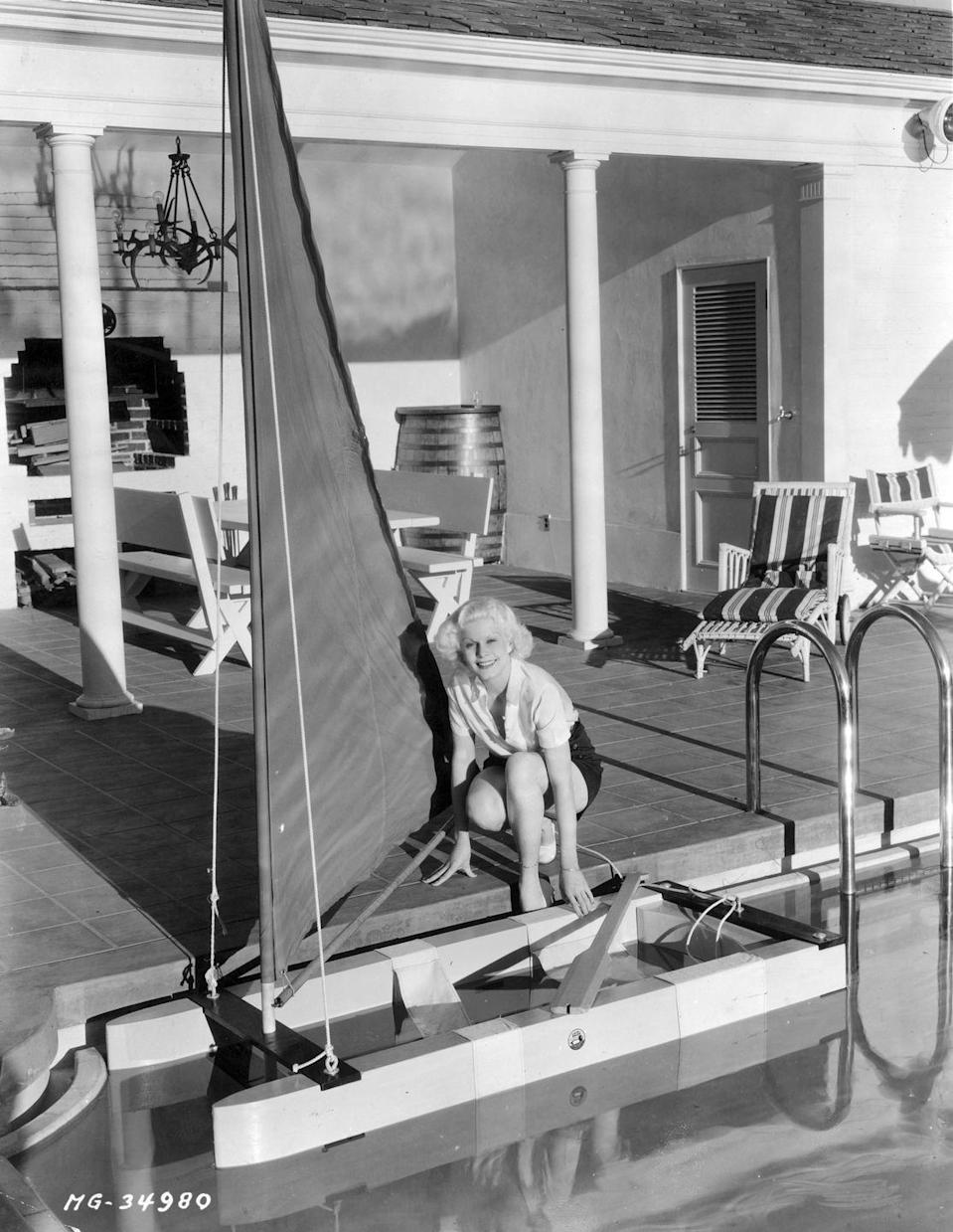 <p>The original blonde bombshell poses poolside next to a small sailboat, circa 1920s.</p>