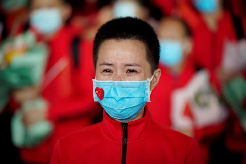 Member of a medical team weeps at the Wuhan Tianhe International Airport