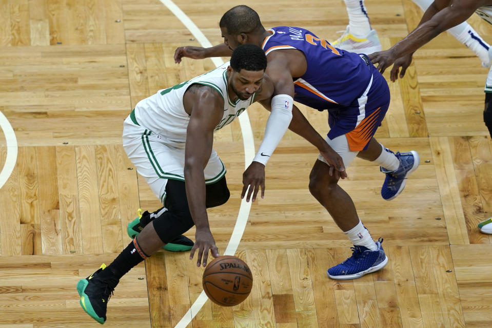 Boston Celtics center Tristan Thompson (13) steals the ball from Phoenix Suns guard Chris Paul (3) in the first quarter of an NBA basketball game, Thursday, April 22, 2021, in Boston. (AP Photo/Elise Amendola)