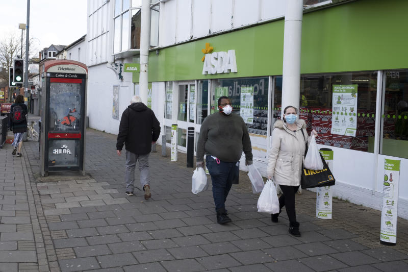 Local response to Coronavirus is felt on a street by street level as people wearing face masks carry their shopping bags outside Asda supermarket on Kings Heath High Street on 6th April 2020 in Birmingham, England, United Kingdom. Coronavirus or Covid-19 is a new respiratory illness that has not previously been seen in humans. While much or Europe has been placed into lockdown, the UK government has announced more stringent rules as part of their long term strategy, and in particular 'social distancing'. (photo by Mike Kemp/In PIctures via Getty Images)