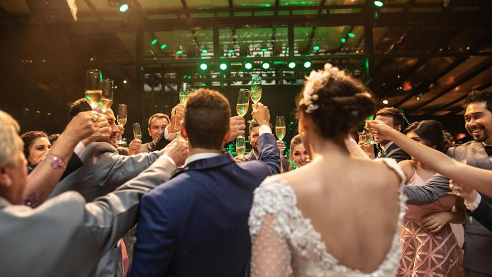 Bride, groom and wedding guests making a toast.