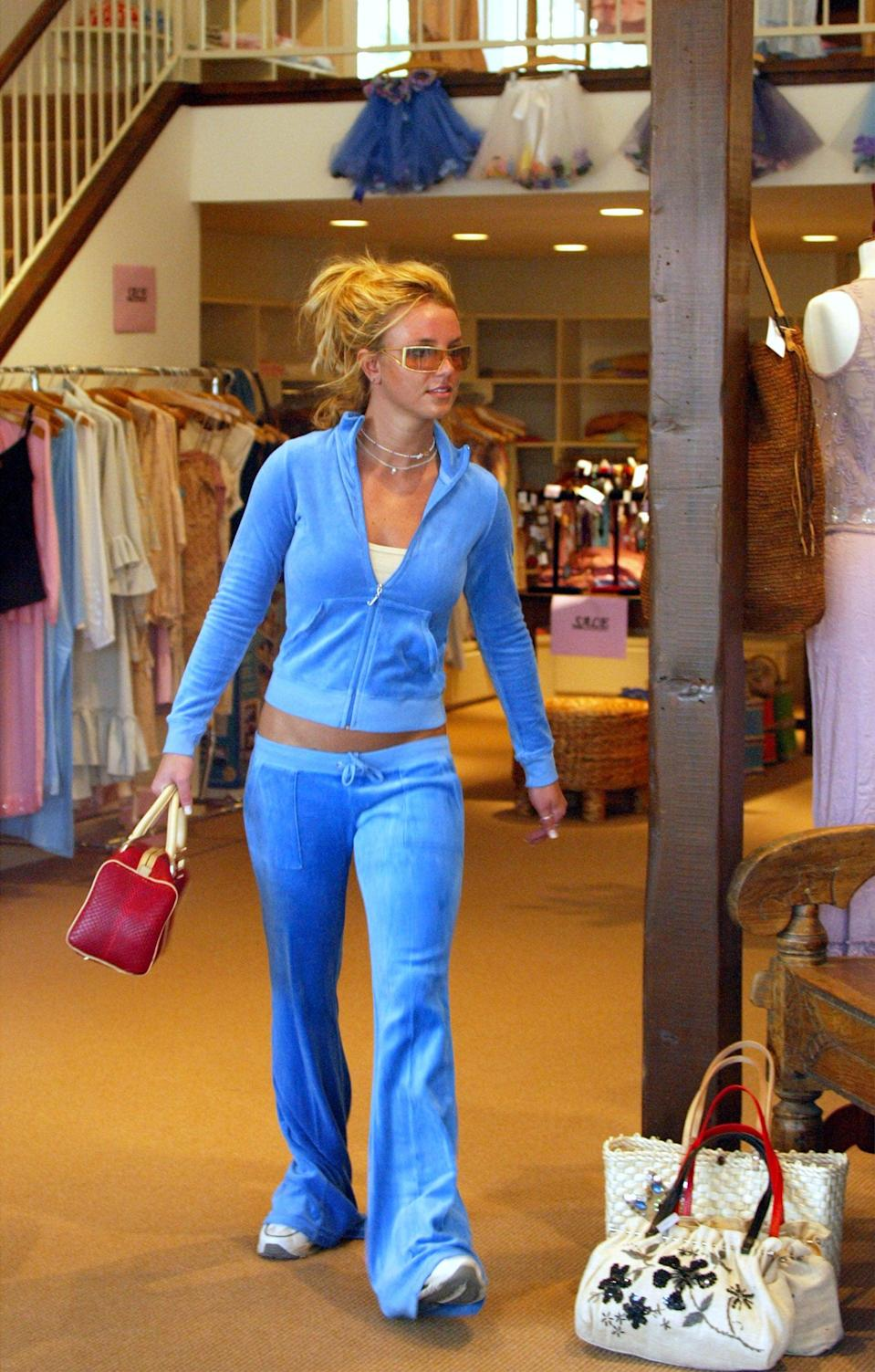 <p>Leaving a store wearing a low-rise Juicy Couture tracksuit. </p>