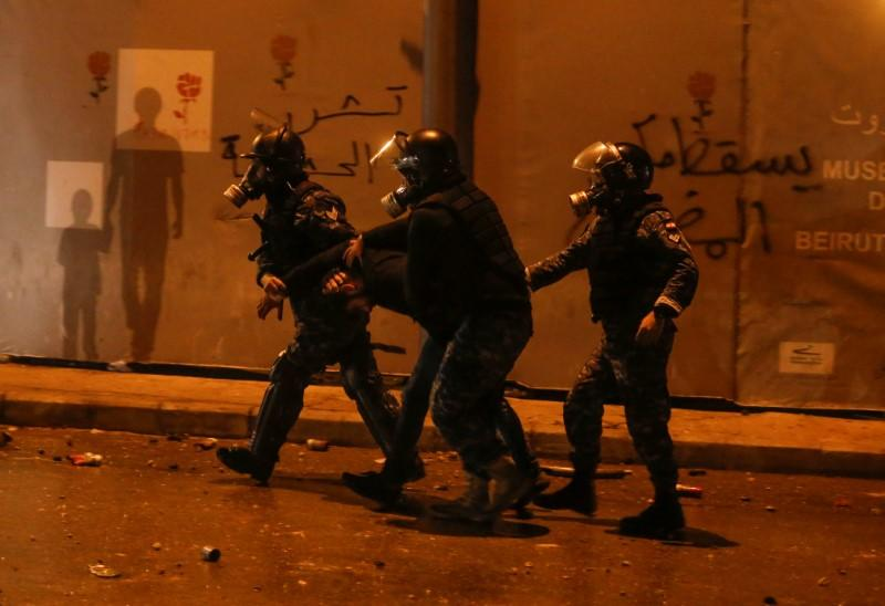 Riot police restrain a protestor during a protest against a ruling elite accused of steering Lebanon towards economic crisis in Beirut