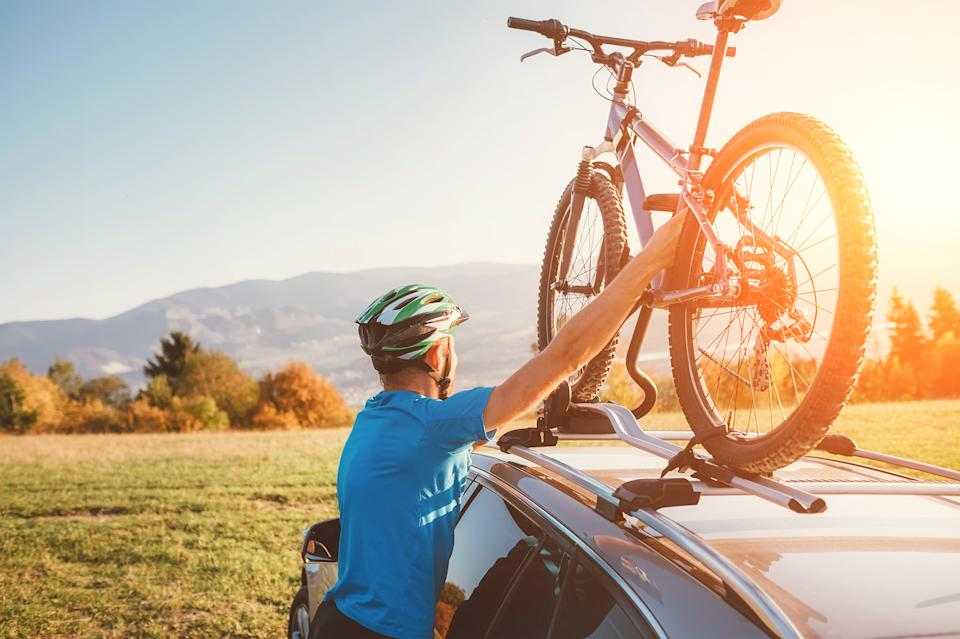 Mountain biker puts bike on car roof. Source: Getty Images