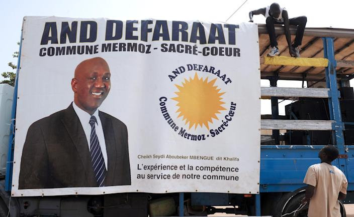 A campaign truck bearing an electoral poster for And defaraat Mermoz-Sacre Cœur party candidate Cheikh Khalifa Mbengue is parked on June 26, 2014, in a street of Dakar, Senegal (AFP Photo/Seyllou)