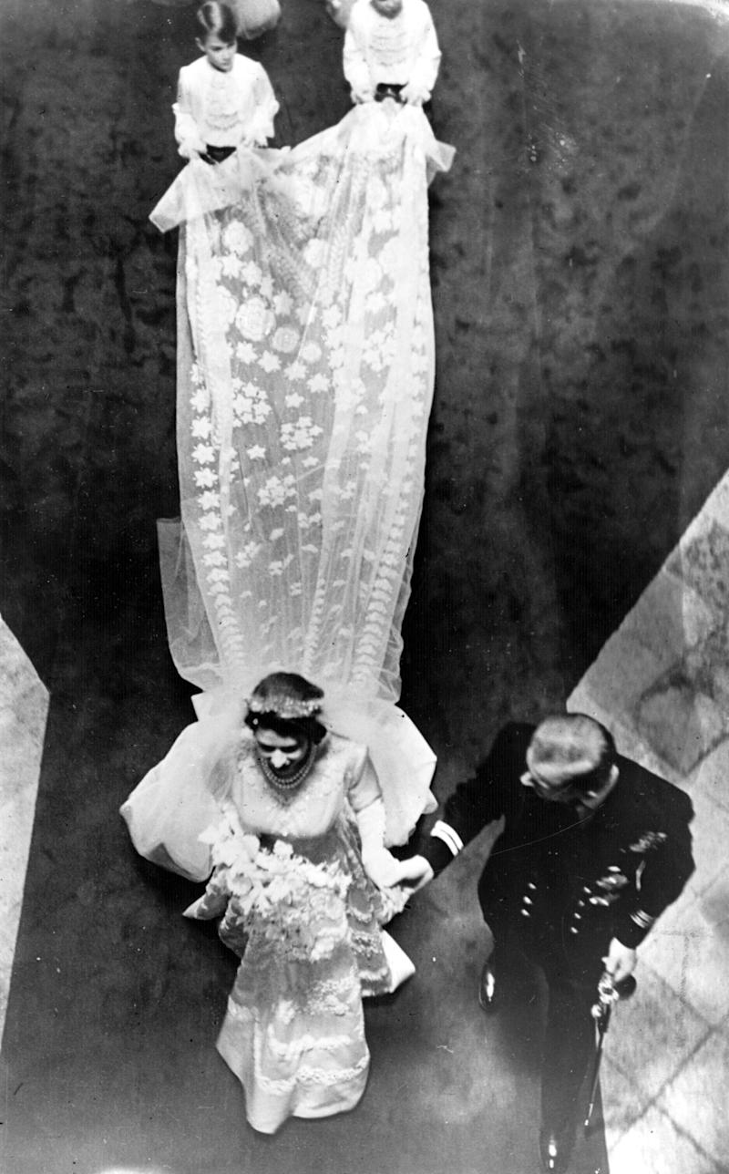 "The future queen wore a gown decorated with crystals and 10,000 seed pearls, <a href=""https://www.royalcollection.org.uk/about/news-and-features/the-queens-wedding-and-coronation-dresses-to-be-displayed-together-for-the#/"" target=""_blank"">designed by Sir Norman Hartnell</a>."