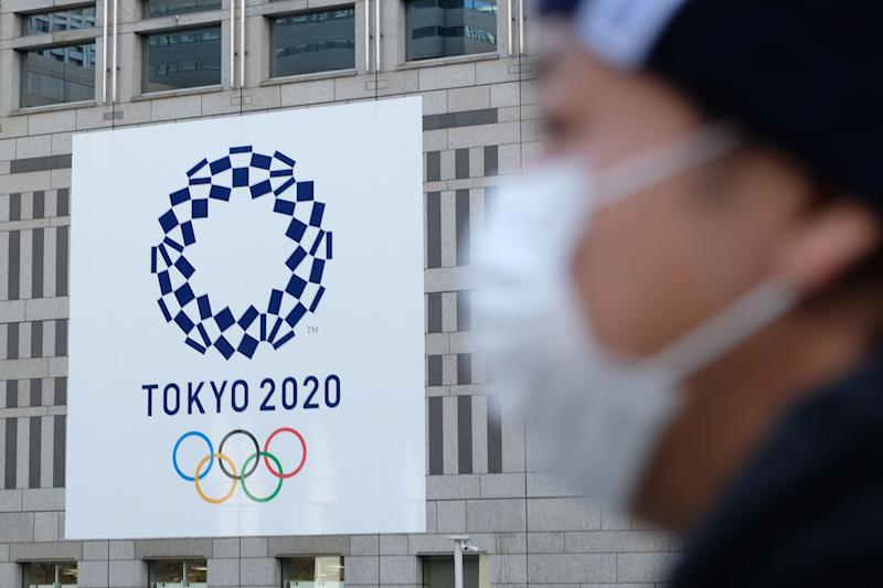 A man wearing a mask passes the logo of the Tokyo 2020 Olympic Games displayed on the Tokyo Metropolitan Government building on March 19, 2020. (Photo by Kazuhiro NOGI / AFP) (Photo by KAZUHIRO NOGI/AFP via Getty Images)
