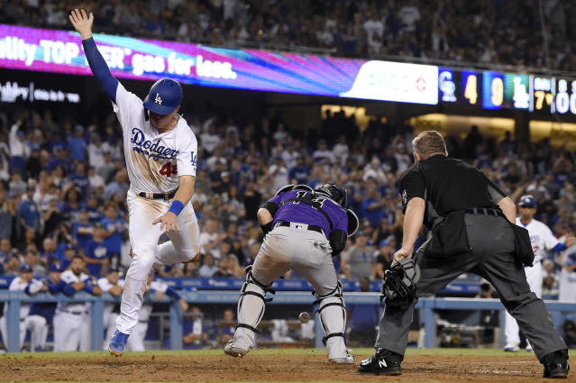 Los Angeles Dodgers' Gavin Lux, left, trips over Colorado Rockies catcher Tony Wolters, center, as he scores on a single by Enrique Hernandez while home plate umpire Greg Gibson watches during the seventh inning of a baseball game Friday, Sept. 20, 2019, in Los Angeles. (AP Photo/Mark J. Terrill)