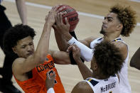 West Virginia's Emmitt Matthews Jr., back, and Miles McBride try to steal the ball away from Oklahoma State's Cade Cunningham during the second half of an NCAA college basketball game in the second round of the Big 12 Conference tournament in Kansas City, Mo., Thursday, March 11, 2021. Oklahoma State won 72-69. (AP Photo/Charlie Riedel)
