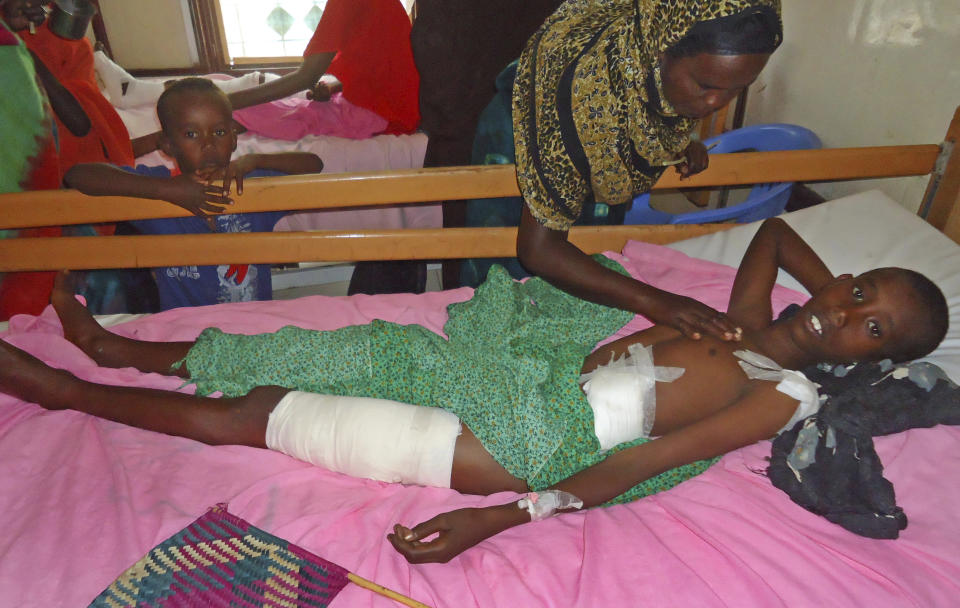A Somali woman comforts her son Abdiftah Adan, 10, as he is treated at Madina hospital in the capital Mogadishu Thursday, Jan. 17, 2013, after he was injured in an African Union (AU) forces attack on his school. AU troops mistakenly opened fire on a religious school in the village of Leggo on Tuesday while pursuing militants, killing five children and two adults, a Somali legislator said Thursday. (AP Photo/Farah Abdi Warsameh)
