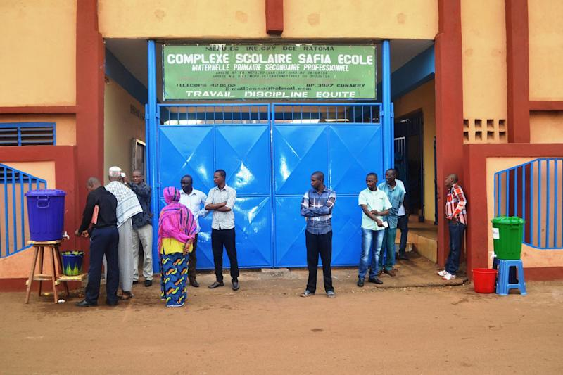 People stand on January 19, 2015 outside the Safia in Conakry as students head back to school after nearly four months of school recess due to the Ebola outbreak
