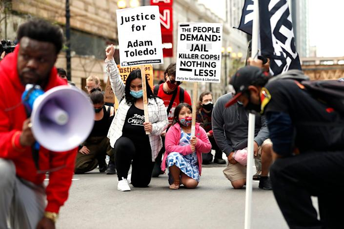 Abigail Garcia, 7, right, takes a knee with her mother Judith Garcia and other protestors during a peaceful protest on Tuesday, April 13, 2021 in downtown Chicago, demanding justice for Daunte Wright and Adam Toledo, who were shot dead by police.