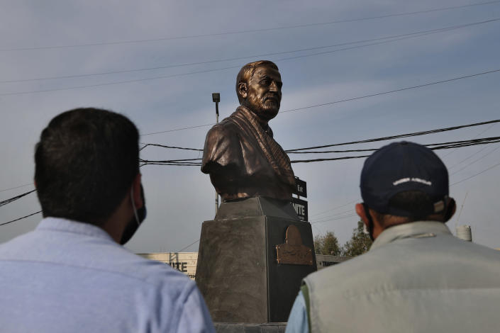 Hezbollah supporters look at a statue of Iranian General Qassem Soleimani, head of Iran's Quds force, installed to commemorate the anniversary of his killing, in a U.S. drone strike in Baghdad, in Ghobeiry, a southern suburb of Beirut, Lebanon, Wednesday, Jan. 6, 2021. (AP Photo/Bilal Hussein)