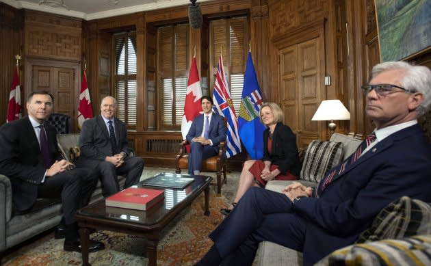 Prime Minister Justin Trudeau speaks before a meeting on the deadlock over Kinder Morgan's Trans Mountain pipeline expansion with B.C. Premier John Horgan, second from left, and Alberta Premier Rachel Notley, as Minister of Finance Bill Morneau, left, and Minister of Natural Resources Jim Carr looks on, in Trudeau's office on Parliament Hill on April 15, 2018.