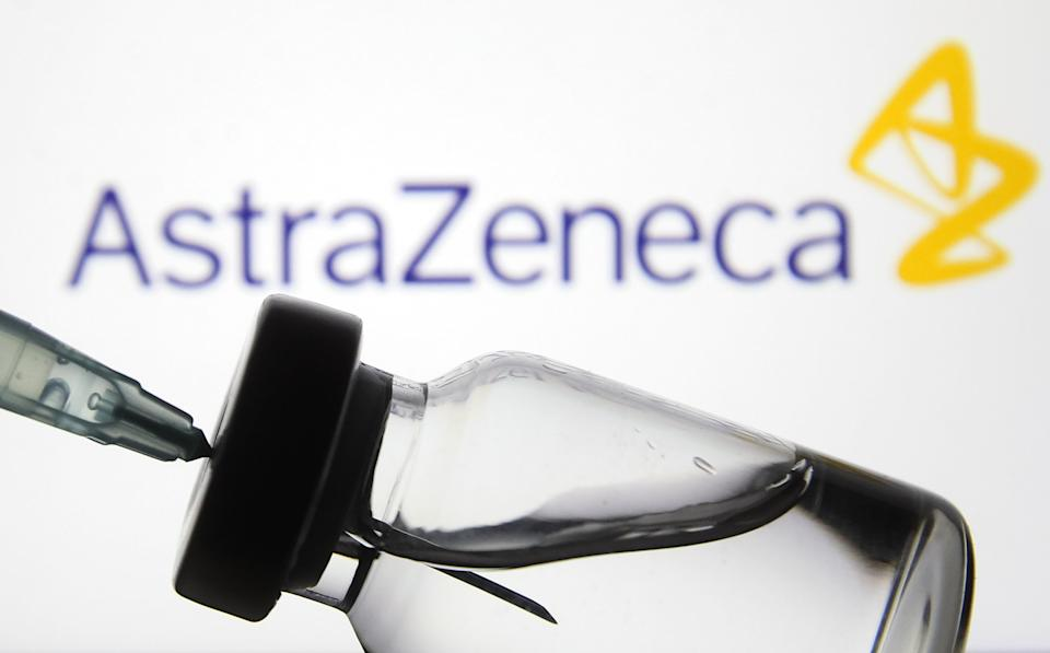 A medical syringe and a vial in front of the AstraZeneca biopharmaceutical company logo are seen in this creative illustrative photo. More than one hundred fifty COVID-19 coronavirus vaccines are in development across the world, several of which have the third phase of clinical trials, as media reported. (Photo illustration by STR/NurPhoto via Getty Images)