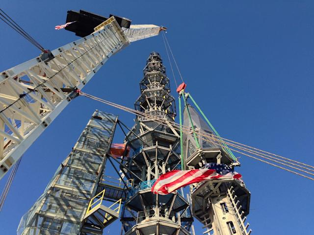 Workers prepare to raise the silver spire atop the 1 World Trade Center building in New York early Friday May 10, 2013. The 408-foot spire will serve as a world-class broadcast antenna. An LED-powered light emanating from it will be seen from miles away. When it is fully installed on the building's roof, it will bring the iconic structure to its full, symbolic height of 1,776 feet. (AP Photo/Mark Lennihan)