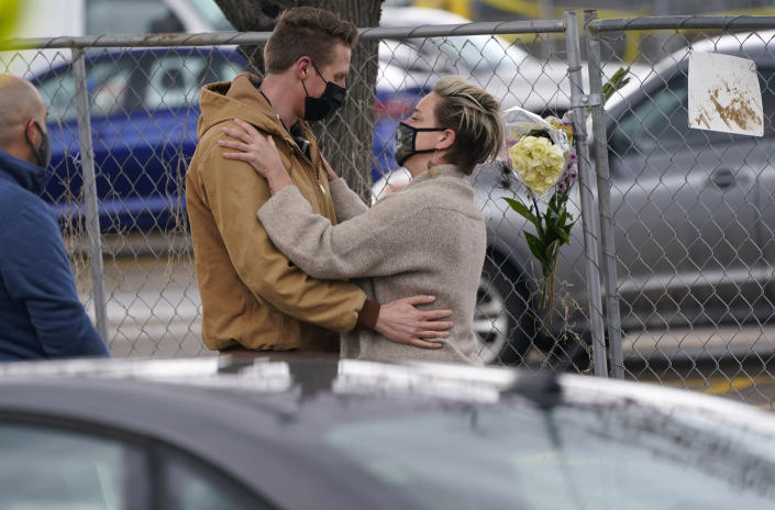 Couple embrace along a fence put up around the parking lot Tuesday, March 23, 2021, where a mass shooting took place in a King Soopers grocery store in Boulder, Colo. (AP Photo/David Zalubowski)