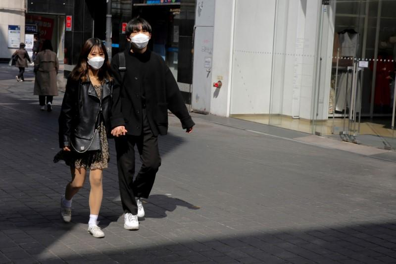 Couple, wearing masks to prevent contracting coronavirus, following outbreak of COVID-19, walk in shopping district in Seoul