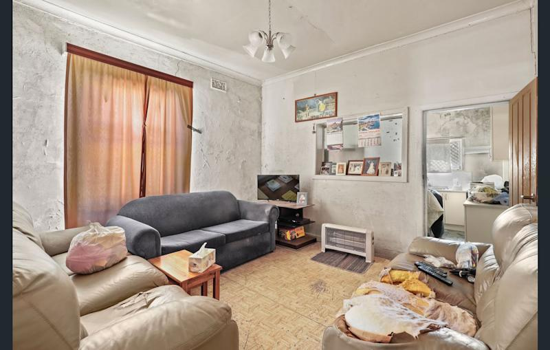 The living room of 25 Pine St, Newtown. The white paint on the walls is peeling off and three couches make up the room.
