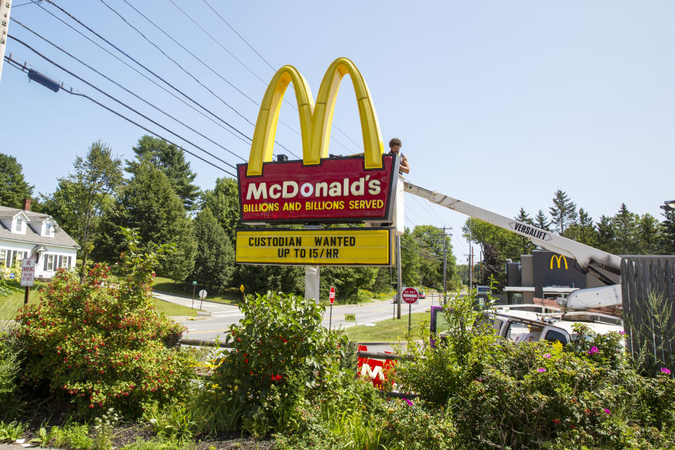 A man works on a McDonald's restaurant sign with a job listing for a custodian paying up to $15 an hour in Bucksport, Maine, on Monday, August 16, 2021. (AP Photo/Ted Shaffrey)